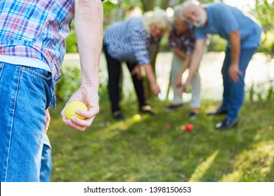 Man is aiming with the ball at the bocce or boules game in the garden with friends