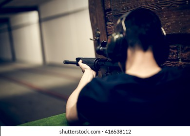 Man aiming M4A1 rifle at target in indoor firing range or shooting range