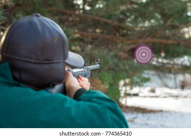 A man aiming a pellet gun towards a target, practicing his aim in the winter.