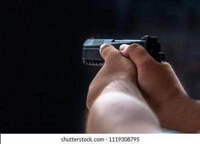 Man aiming pistol in shooting range.