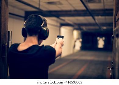 Man aiming pistol at target in indoor firing range or shooting range