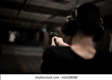 Man aiming revolver pistol at target in indoor firing range or shooting range