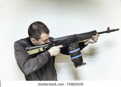 a Man is Aiming with Saiga Hunting Rifle. Video Card for the Place of the Magazine with Bullets. Gaming Illustration with Serious Hardware Setup