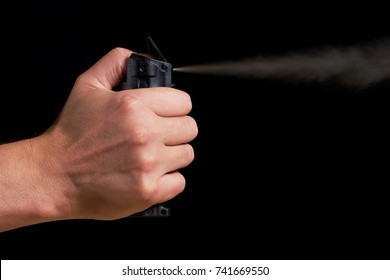 man aiming and spraying pepper spray with visible fog on black background