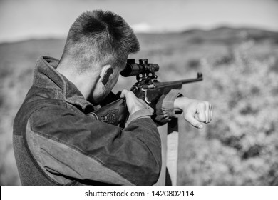Man aiming target nature background. Aiming skills. Hunter hold rifle aiming. On my target. Bearded hunter spend leisure hunting. Hunting optics equipment for professionals. Brutal masculine hobby.