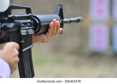 Man aiming at a target and shooting an automatic rifle for