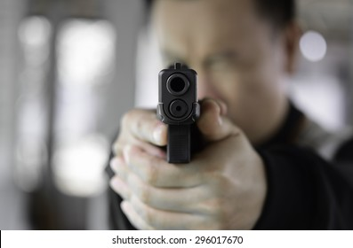 A man aims his semi automatic pistol. Selectively focused on the front of the gun.