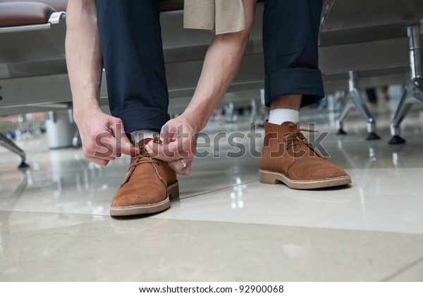 Man in airport lacing his suede shoes