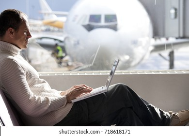 man in an airport with a laptop