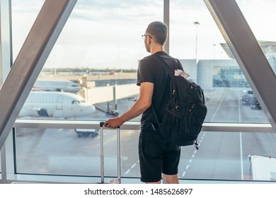 Man in airport near gate windows at planes on runway.