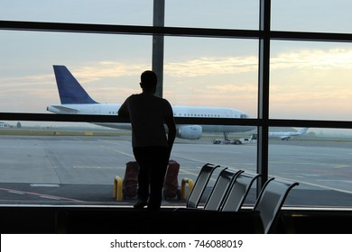 Man in the airport with plane on the background. Waiting for a trip