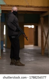 A man airsoft gunman in a black mask on his face posing with an akm machine gun in his hands in an abandoned room