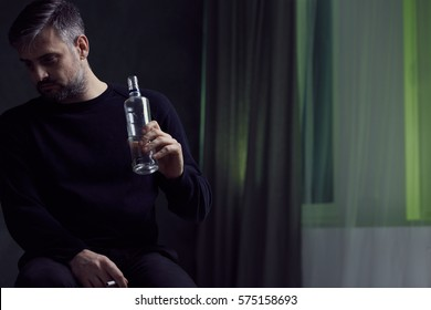 Man with alcohol addiction in gloomy room