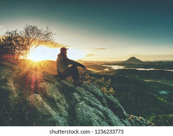 Man alone ath edge. Hiker enjoy view into fairy landscape. Sharp sun rays
