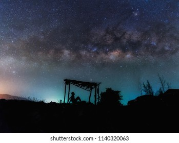 A man alone in old shack and Milky way Panorama ,Astrophotography and Nightscape photography, Milky way over the old shed in Thailand