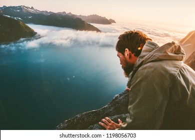 Man alone on the edge cliff above sea looking down into abyss traveling in mountains adventure lifestyle extreme vacation
