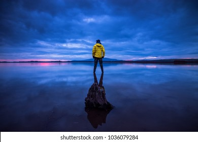 Man alone at Sea during sunset, winter, yellow jacket, blue hour