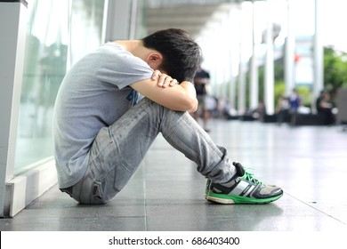Man alone sitting in the corner strained unhappy depressed, destroyed, wasted and sad suffering