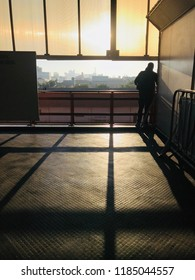 Man alone in the subway watching the sunrise
