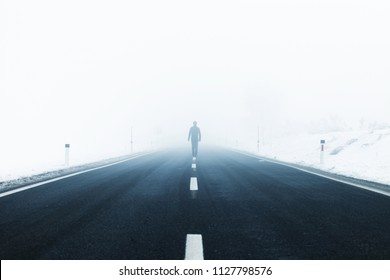 Man alone walks in the middle of the foggy asphalt road.