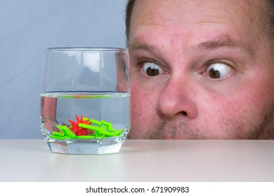 A man is amazed at colibacteria (Escherichia coli),  germs and viruses in a glass of water