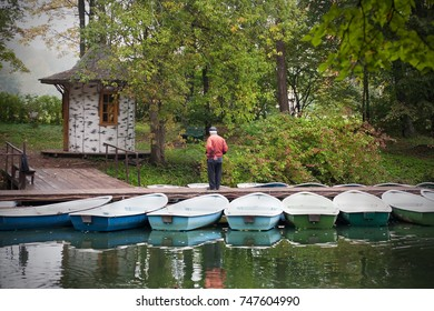 Man among boats on pier in forest. Fisherman in red shirt
