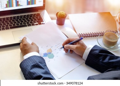 Man analysis business accounting on paper chart and laptop.