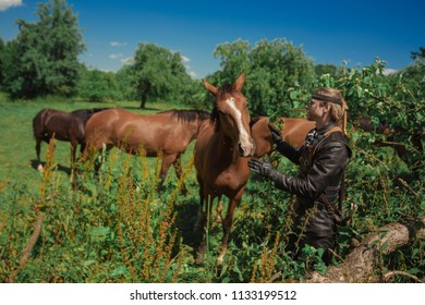 A man in an ancient leather suit of a knight with horses in the forest - Shutterstock ID 1133199512