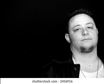 Man with angry, or frustrated expression in black and white.