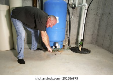 Man with angry, red face bent over well pump with a wrench