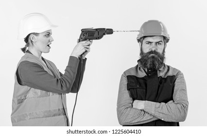 Man with annoyed face in helmet. Family making repair, husband annoyed by wife. Builder makes hole in male head. Annoying repair concept. Woman with happy face drills head of man, white background.