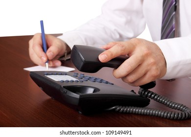 man is answering or hanging up the phone in an office