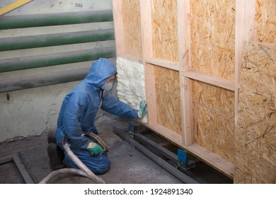 A man applies an insulating foam to the wall of the house
