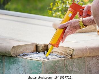 Man applying cement adhesive with a caulk gun tool. Repairing broken concrete paver stone swimming pool tile.