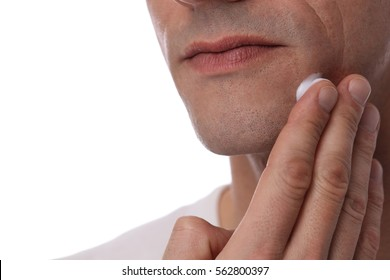 Man applying moisturizer cream on his face skin on white background.