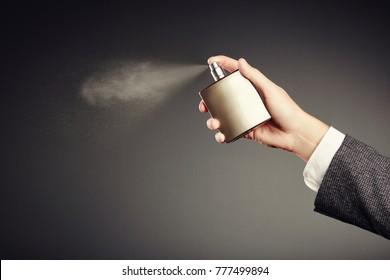 Man applying Perfume. Man's Perfume in the Hand on Black Background