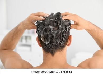 Man applying shampoo onto his hair against light background