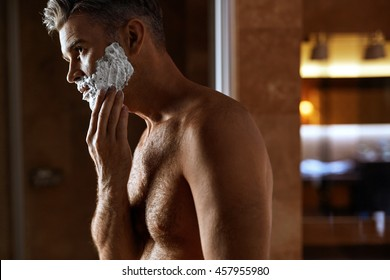 Man Applying Shaving Cream On His Face Standing In Bathroom. Portrait Of Male With Naked Upper Body Putting Shaving Foam On His Beard. Skin Care Concept