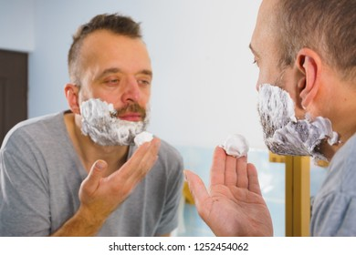 Man applying shaving foam cream on his face, standing in bathroom, looking at mirror, preparing to shave his face beard. Skincare