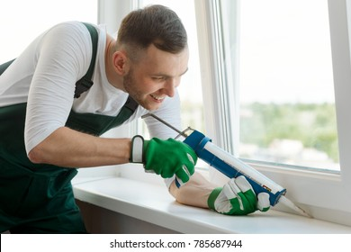 Man applying silicone sealant between window sash and sill. Home repair and renovation, handyman for an hour service.