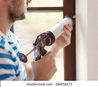 Man applying silicone sealant with caulking gun