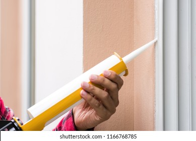 The man applying silicone sealant. The man fixing home.