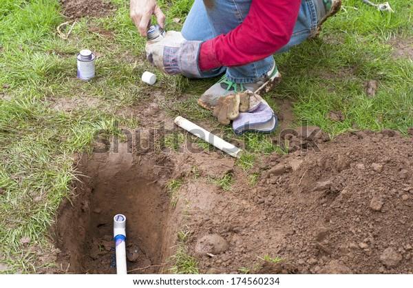Mann, der Solvent Primer und Cement auf PVC-Rohre als Teil der Installation des Untergrundautomatisches Sprinklersystem zum Watering von Garten und Rasen anwendet