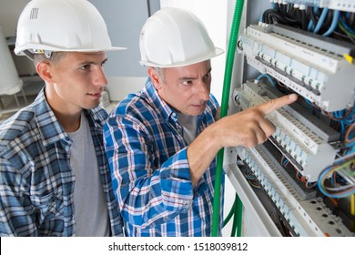 man and apprentice electrical distribution fuse board