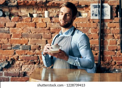 a man in an apron is behind the counter in a cafe