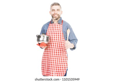 Man in apron with cooking utensils on white background