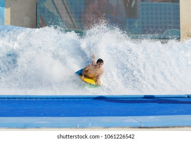 man in aqua park surfing with big wave