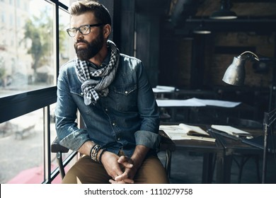 Man architect with dark hair and beard, weared in denim jacket, scarf and glasses is sitting in the modern office near the window with architectural plan on the table behind him