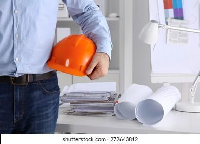 Man architect wearing suit holding  helmet.