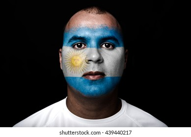 Man with Argentina flag painted on  his face on black background